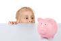 Funny little girl hiding behind white table and looking at pink ceramic piggy bank