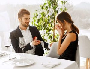 Love. Romantic Couple Relationship. Closeup Of Handsome Man Making Proposal Of Marriage To Beautiful Woman With Engagement Diamond Ring In Luxury Gourmet Restaurant. Wedding, Romance Concept.